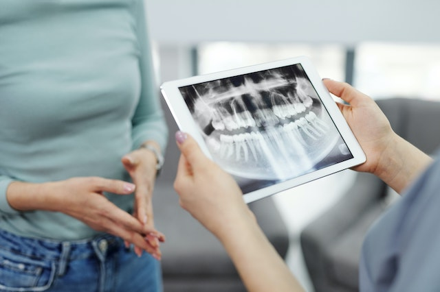 Dental patient holding a tablet with digital x-rays on it