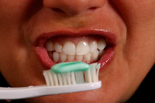 A close up photo of a person smiling, holding a toothbrush with toothpaste on it in front of their mouth.