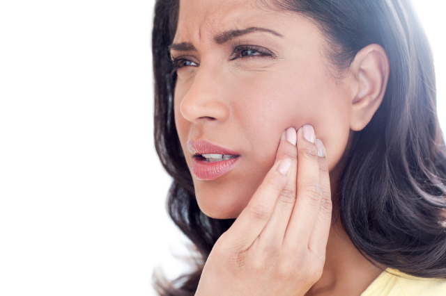 A closeup of the face of a brunette woman. She is holding her hand up to her jaw and making a face as if she is in pain.